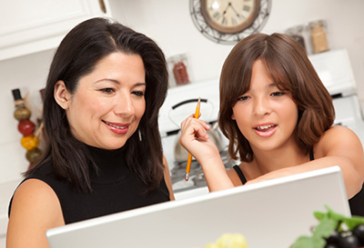 Mother and daughter test their knowledge by taking the Financial Literacy Assessment Test online.